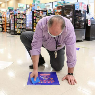 Shoprite manager John Coyle applies a sticker provided by Mural Arts. The stickers are intended as cheerful reminders to keep a safe distance in the store's crowded checkout aisles. (Emma Lee/WHYY)